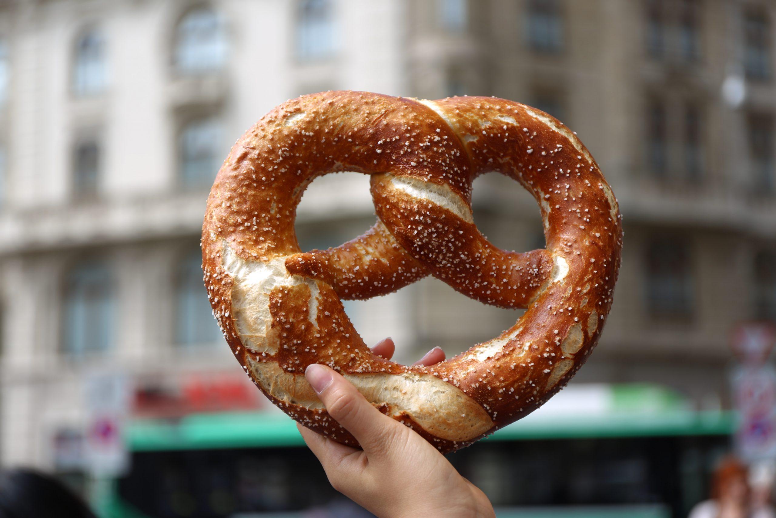 person holding soft pretzel